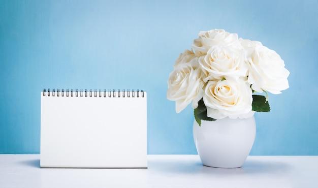 Calendário de mesa em branco com flores rosas brancas