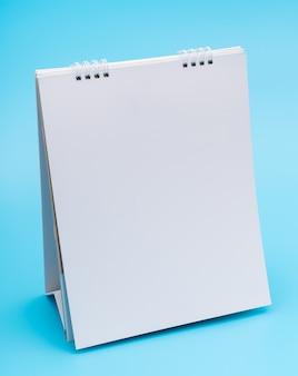 Calendário de mesa em branco com páginas, isolado no fundo azul.