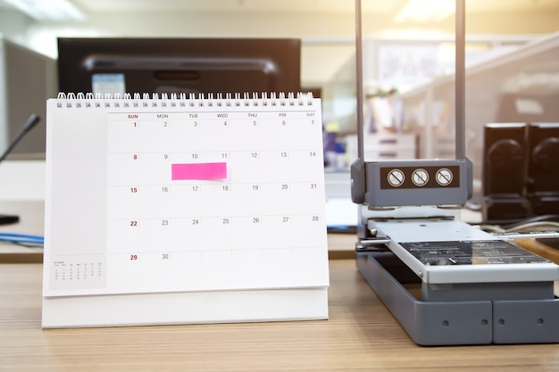 Calendário de mesa em branco de close-up com nota de papel.