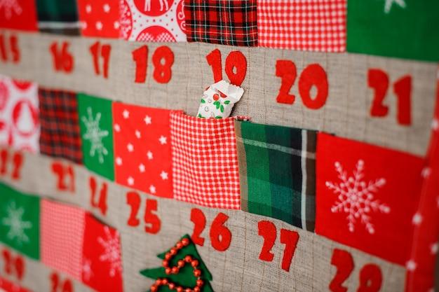 Calendário de natal macio e têxtil com bolsos na parede