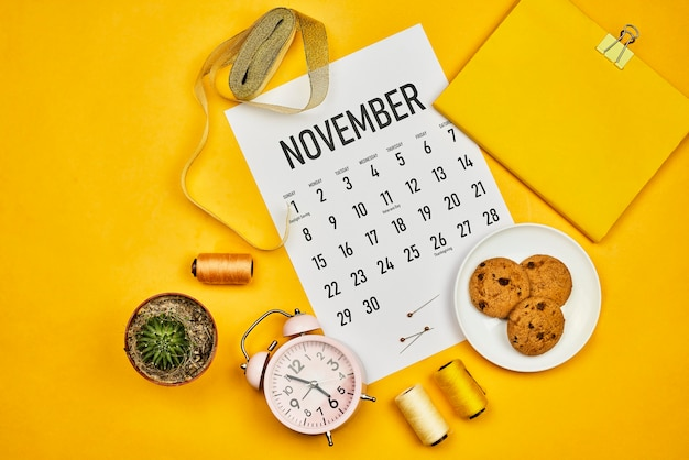 Calendário de novembro na área de trabalho amarela brilhante. o espaço de trabalho luminoso de uma costureira ou estilista