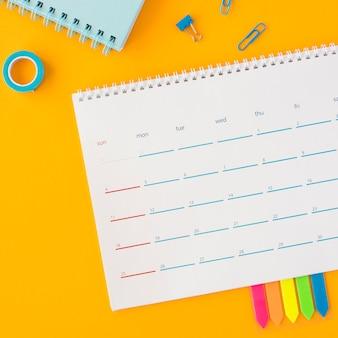 Calendário de papelaria de vista superior com ferramentas de escritório