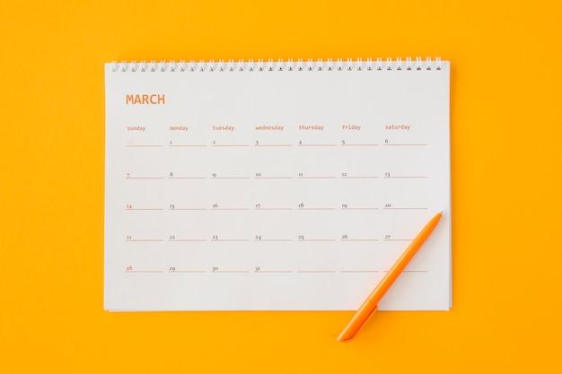 Calendário de papelaria de vista superior com lápis laranja