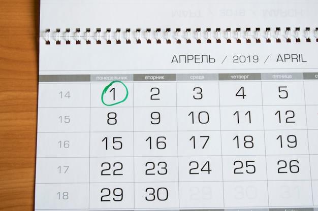 Calendário de parede com o mês de abril, 1º de abril a dia da mentira, circulado com um círculo verde