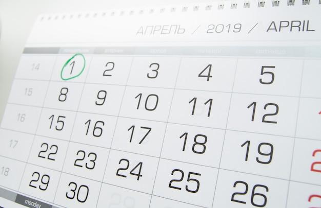 Calendário de parede com o mês de abril, 1 de abril a dia da mentira, circundado por um círculo verde, luz