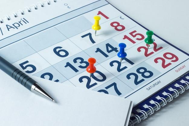 Calendário de parede e caneta, dias importantes são marcados com knops