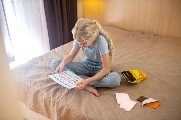 Calendário de períodos. uma adolescente loira, marcando os dias de sua menstruação em um calendário