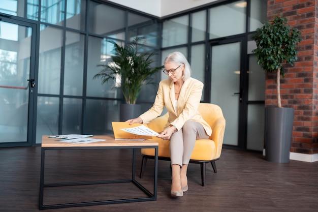 Calendário de planejamento. mulher de negócios sênior séria sentada à mesa no escritório enquanto olha para um calendário de planejamento na mão