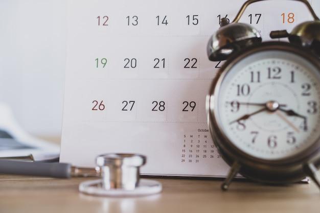 Calendário, despertador e estetoscópio na mesa do médico