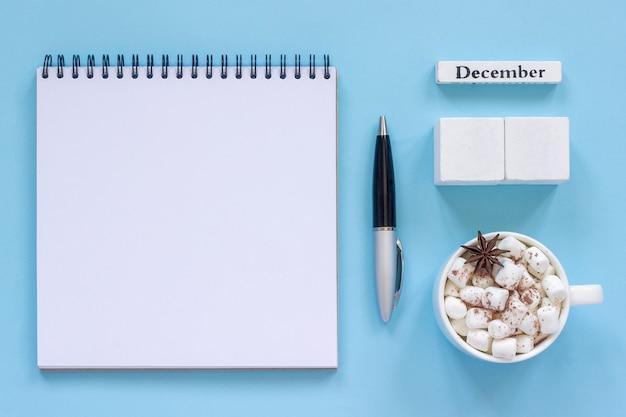 Calendário dezembro xícara de cacau e marshmallow, bloco de notas aberto vazio