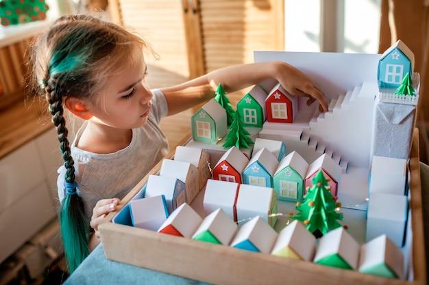Calendário do advento de origami. linda garota olhando para pequenas casas de papel com número