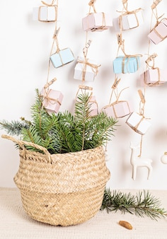 Calendário do advento feito à mão com caixas de presente penduradas em cordas e agulhas de pinheiro em uma cesta de vime