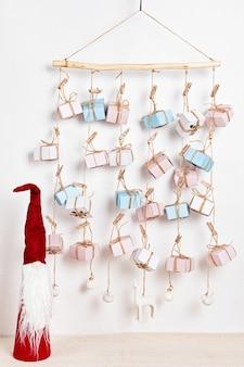 Calendário do advento feito à mão com caixas de presente penduradas em cordas e estatueta de papai noel