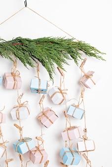 Calendário do advento feito à mão com caixas de presente penduradas em cordas