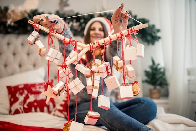 Calendário do advento nas mãos de uma menina, uma surpresa em uma caixa, presentes de natal.