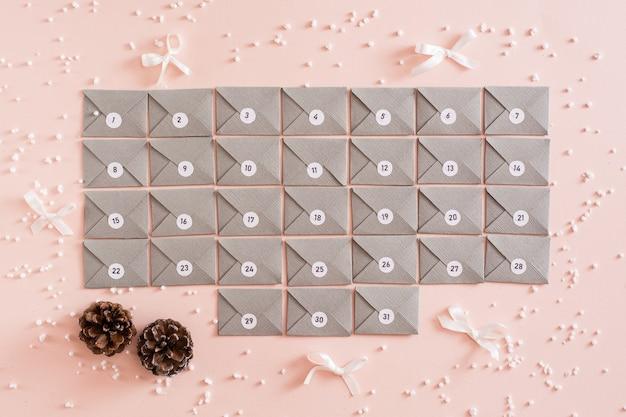Calendário do advento pronto com envelopes de papelão cinza em uma mesa em decorações de natal