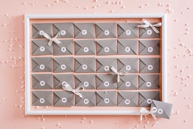 Calendário do advento pronto com envelopes de papelão cinza em uma moldura branca em uma mesa com decorações de natal