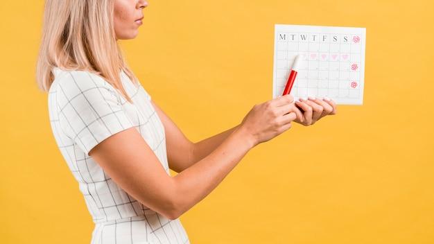 Calendário do período com formas de coração desenhadas e mulher de lado