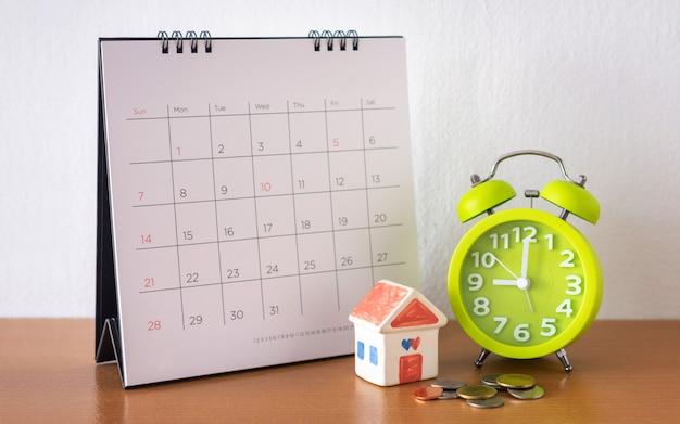 Calendário e casa na mesa. dia de compra ou venda de uma casa ou pagamento de aluguel ou empréstimo.