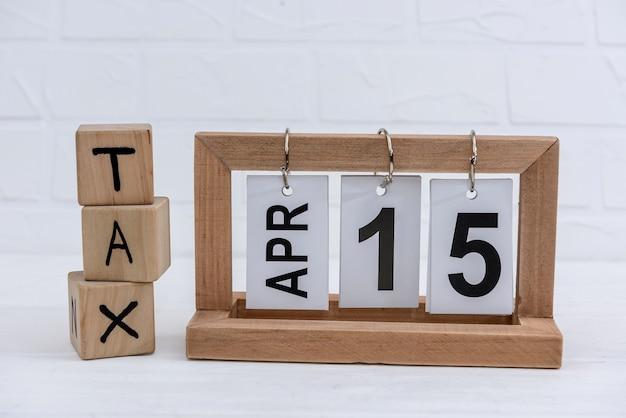 Calendário e cubos de madeira com a palavra 'imposto'