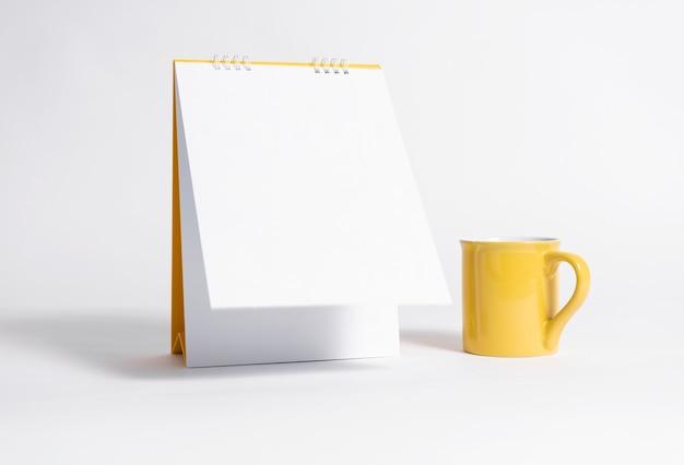 Calendário espiral de papel em branco e copo amarelo para modelo de maquete