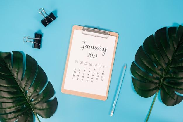 Calendário liso da configuração com prancheta, folhas de palmeira e lápis no fundo azul.