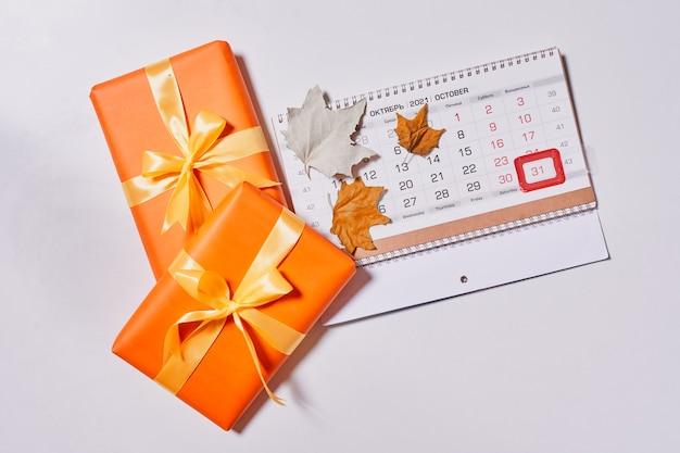 Calendário mensal de outubro e caixas de presente no fundo branco vista superior vista aérea do mês de outono ...