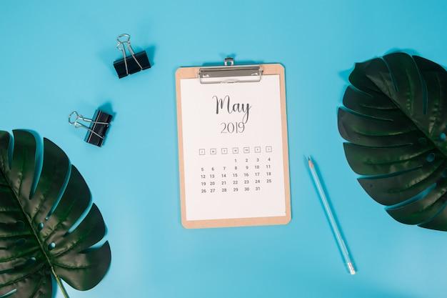 Calendário plana leigos com prancheta, folhas de palmeira e lápis sobre fundo azul
