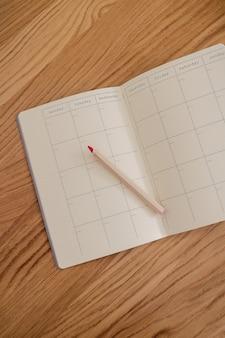 Calendário vazio e em branco e diário aberto visto de cima com um lápis ao lado dele. planejar e fazer o conceito de lista. cores amarelas e cinza do ano.