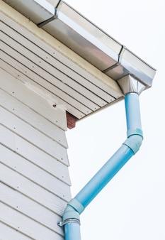 Calha de telhado com o cano de esgoto