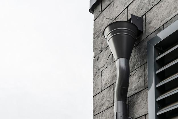 Calha do telhado montada na parede do edifício forrada com ladrilhos de pedra modernos preto e marrom elegante design moderno elemento close up
