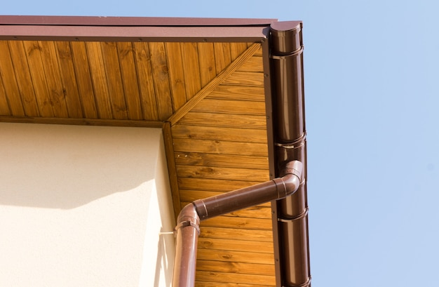 Calhas e cano de esgoto recém-instalados nos beirais de madeira de uma nova casa construída em construção