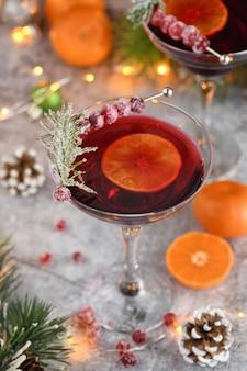 Cálice com cranberry margarita com cranberries cristalizadas, alecrim e tangerina. coquetel perfeito para uma festa de natal