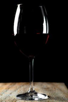 Cálice de cristal com vinho tinto na mesa rústica de madeira