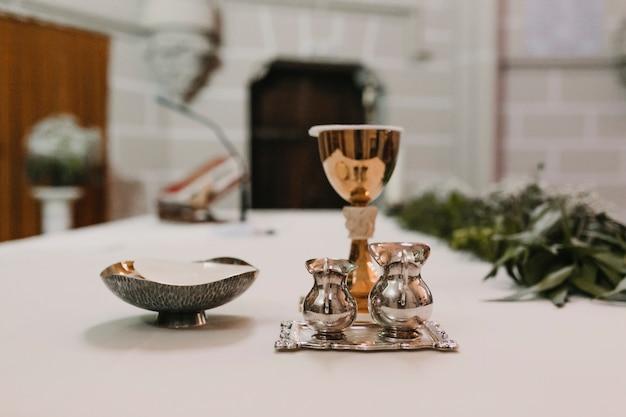 Cálice de vinho na mesa durante uma missa nupcial de cerimônia de casamento. conceito de religião. ornamentos da eucaristia católica para a celebração da eucaristia