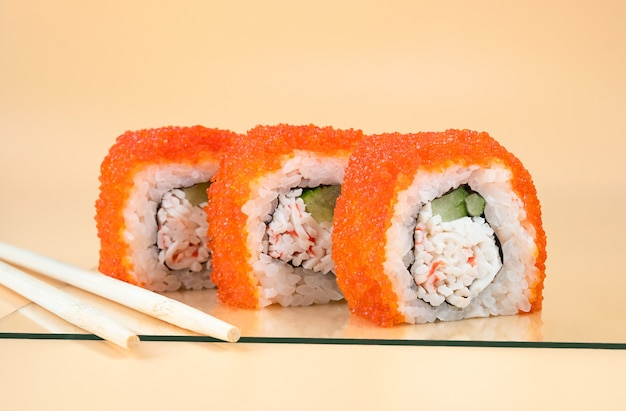California roll sushi com pepino, abacate, caranguejo e masago laranja em fundo laranja claro