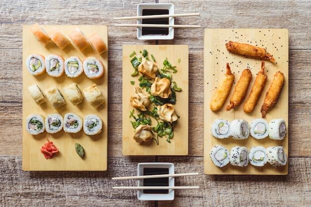 Califórnia sushi roll, rolo de sushi de saquê, camarões fritos, gyozas e molho de soja em uma mesa de madeira