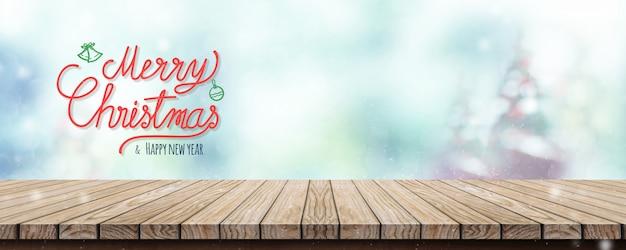 Caligrafia feliz natal e feliz ano novo sobre a mesa com árvore de natal de borrão e sno