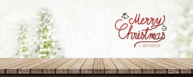 Caligrafia feliz natal e feliz ano novo sobre a mesa de madeira com árvore de natal de borrão