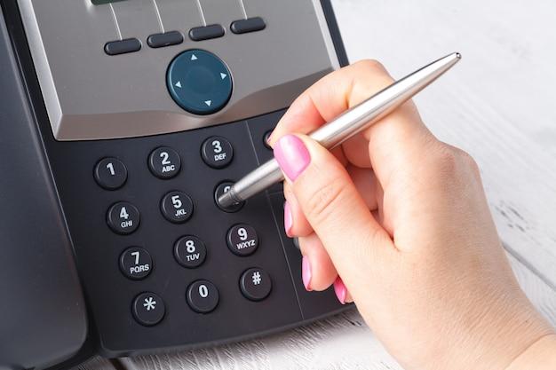 Call center ou escritório telefone conceito, dedo feminino pressione o número no telefone