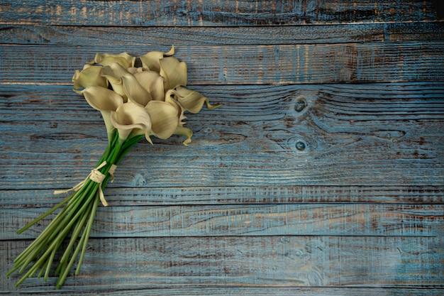 Calla amarelo flores sobre fundo azul de madeira