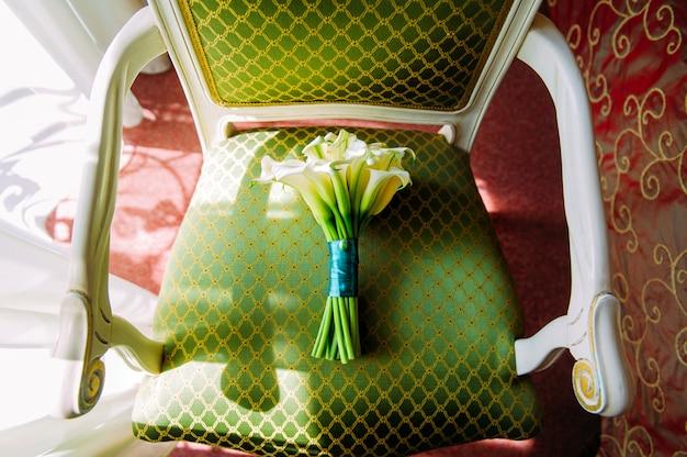 Calla, um lindo buquê para a noiva, vista superior. buquê de casamento em uma cadeira na luz solar, close-up.