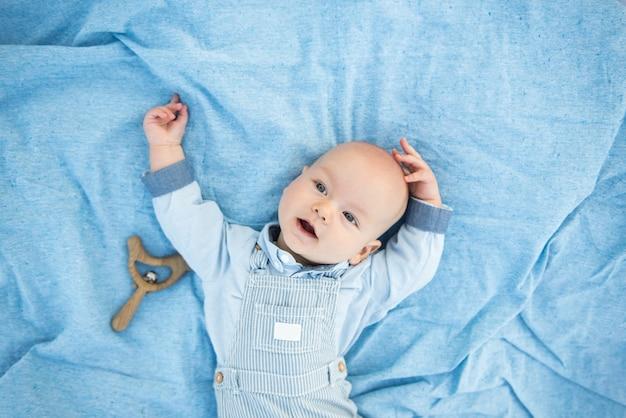 Calma bebê curioso deitado sobre fundo azul, olhando para a câmera, vista de cima