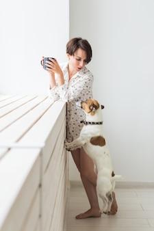 Calma e aconchego. mulher jovem e bonita com uma xícara de chá e cachorro em pé perto da janela em casa