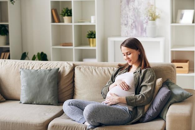 Calma e atraente jovem grávida sentada com as pernas cruzadas no sofá e abraçando a barriga
