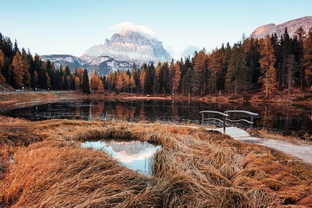 Calma e beleza. vista incrível das montanhas majestosas com madeiras na frente deles no dia de outono. poça que sai do lago com uma pequena ponte no centro