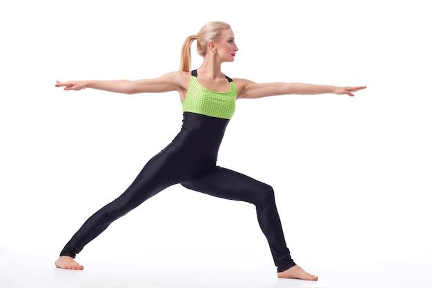 Calma e paz. foto de estúdio de uma mulher saudável e em forma fazendo ioga em pé em uma posição de guerreiro, exercitando-se isolado no branco copyspace