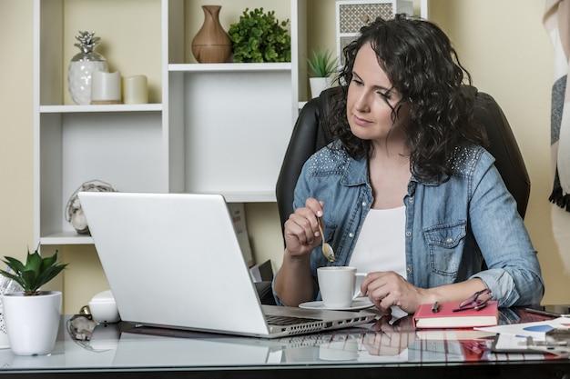 Calma empresária pensativa usando laptop enquanto tomando café no escritório moderno