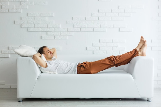 Calma empresário bonito dormindo no sofá depois do trabalho em casa