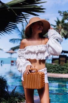 Calma, feliz e elegante garota usando shorts de malha branca e blusa de mangas compridas segurando uma bolsa de cesta de piquenique de vime